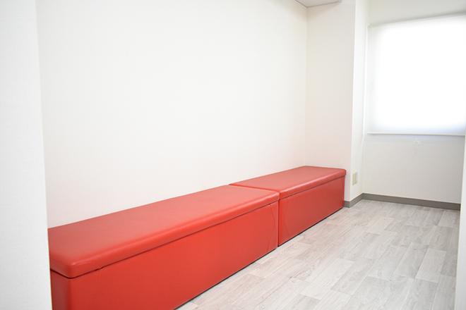 白に映えるビビッドな赤の長椅子を設置